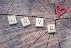Imagem da palavra amor ecrita em inglês - LOVE - sobre um tronco de madeira e ao lado a imagem de um coração.