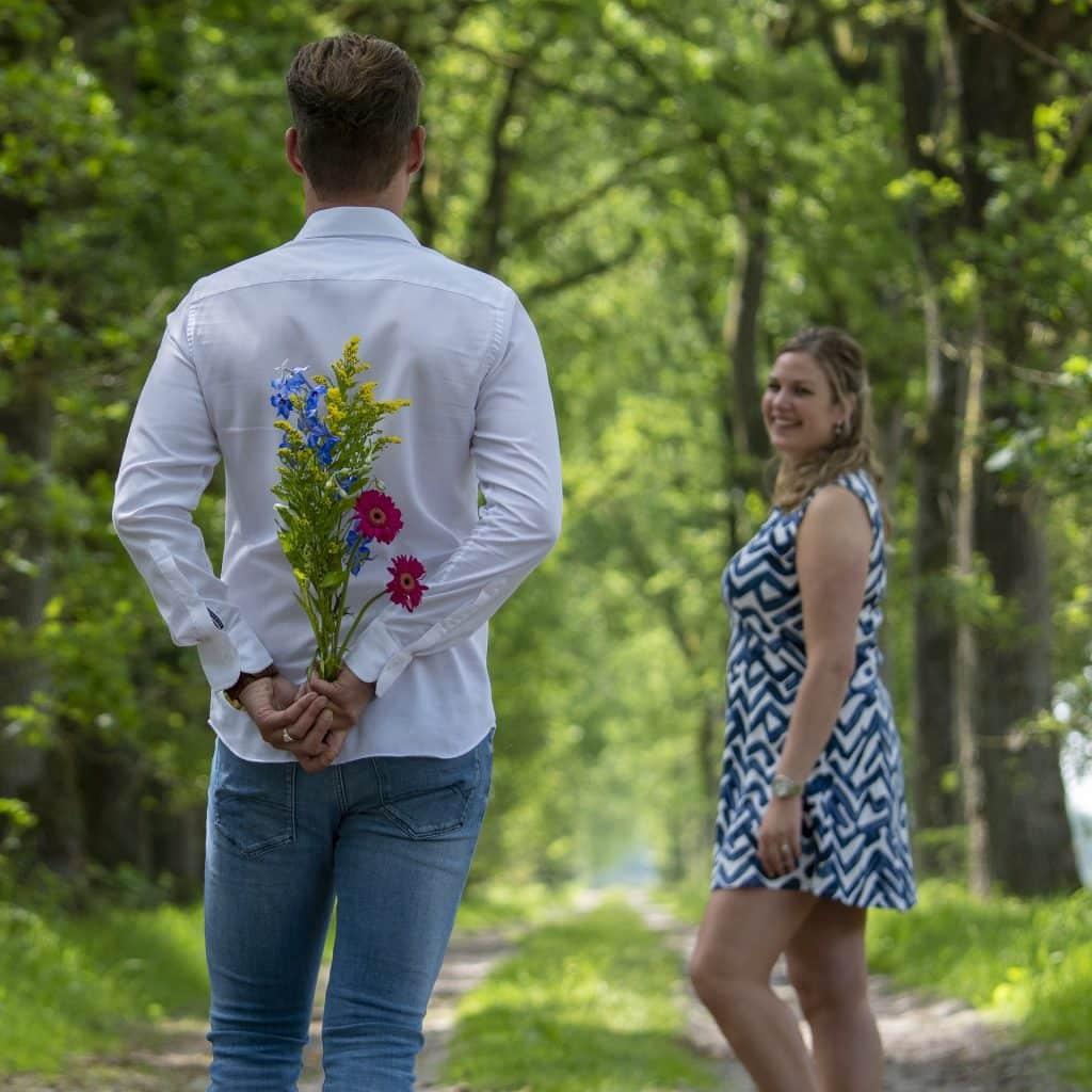 Imagem de um casal em um parque arborizado. O rapaz esconde um lindo buquê de flores para entregar para a sua amada. É uma demonstração de amor e afeto.
