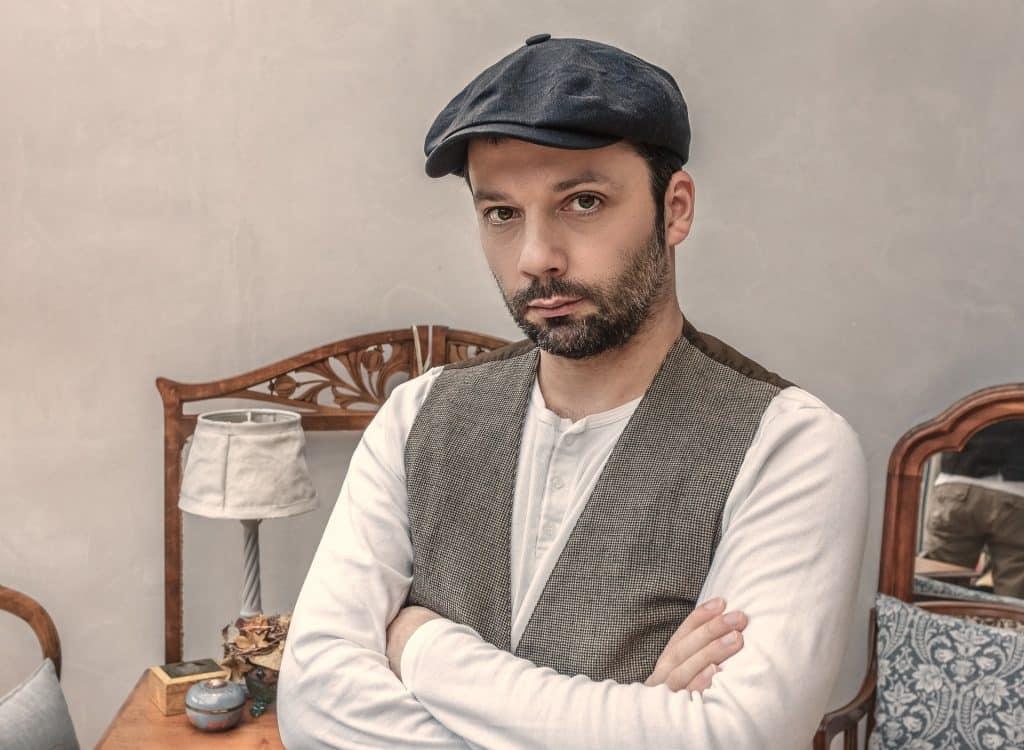 Imagem de um homem de barba cerrada. Ele usa uma camiseta branca de manga longa, uma boina preta e um colete cinza. Ele está de braços cruzados e de mau  humor.
