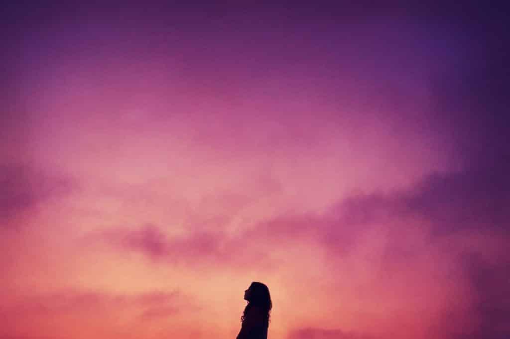 Silhueta de uma mulher vista de perfil ao pôr do sol.