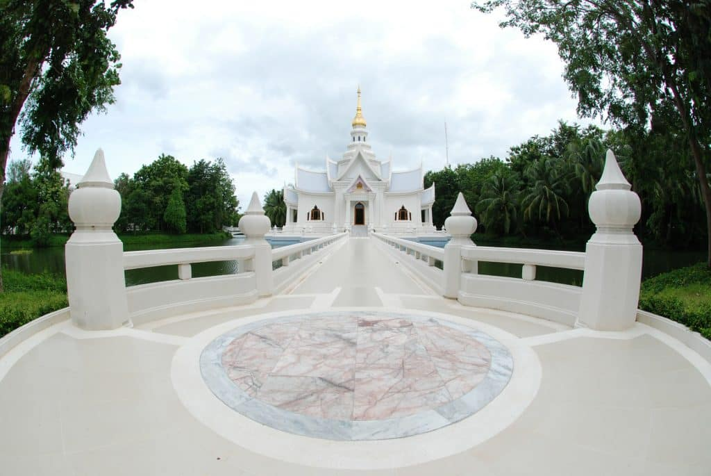 Imagem de um retiro espiritual em um templo budista. Trata-se de um prédio todo branco e muito grande.