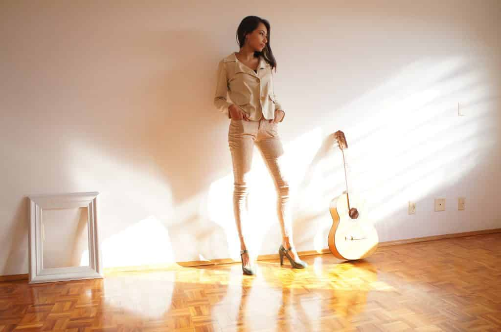Imagem do corpo de uma linda mulher. Ela está encostada na parede da sua sala. Usa um lindo terno e calça na cor bege. Ao lado dela um violão e uma moldura para foto.