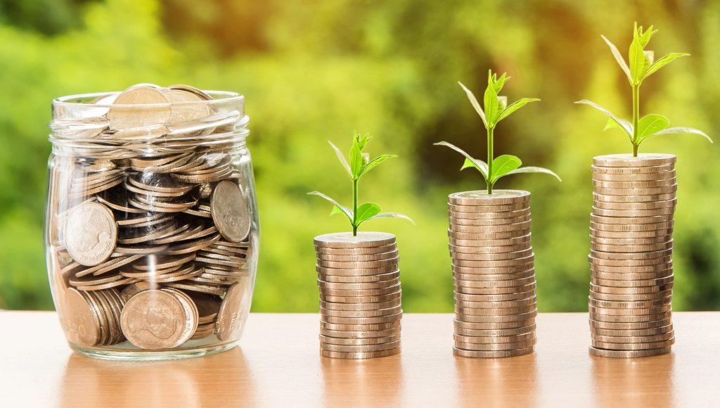 Imagem de um pote de vidro cheio de moedas douradas. Ao lado dele três montinhos da mesma moeda e sobre eles uma plantinha nascendo.