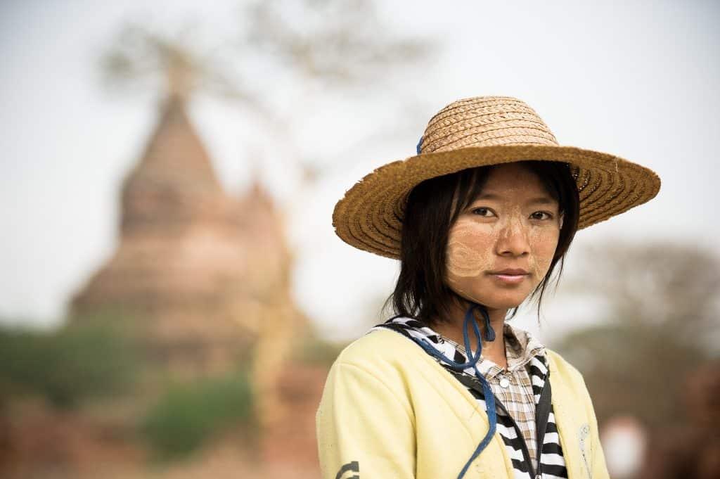 Imagem de uma linda jovem oriental. Ela usa sobre a sua cabeça um chapéu de palha para se proteger do sol.