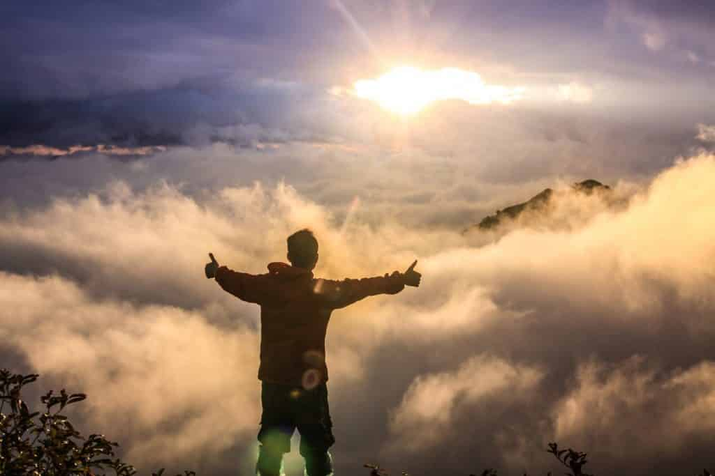 Homem de costas e braços abertos no topo de uma montanha acima das nuvens.