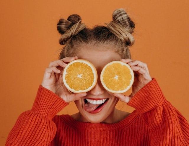 Mulher com laranjas em frente aos olhos mostrando a língua em fundo laranja