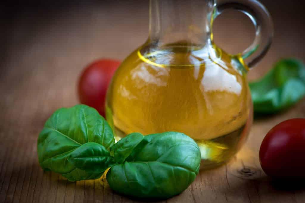 Imagem de uma garrafa de vidro com óleo de chia. Ao lado, folhas de manjericão e tomates cerejas.