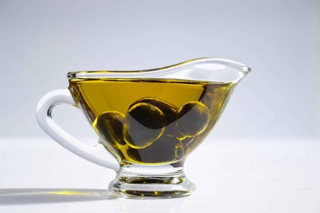 Imagem de um suporte de vidro contendo azeite de oliva.