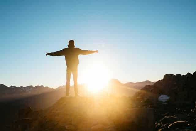 Homem em pé de costas em montanha com sol refletindo ao fundo