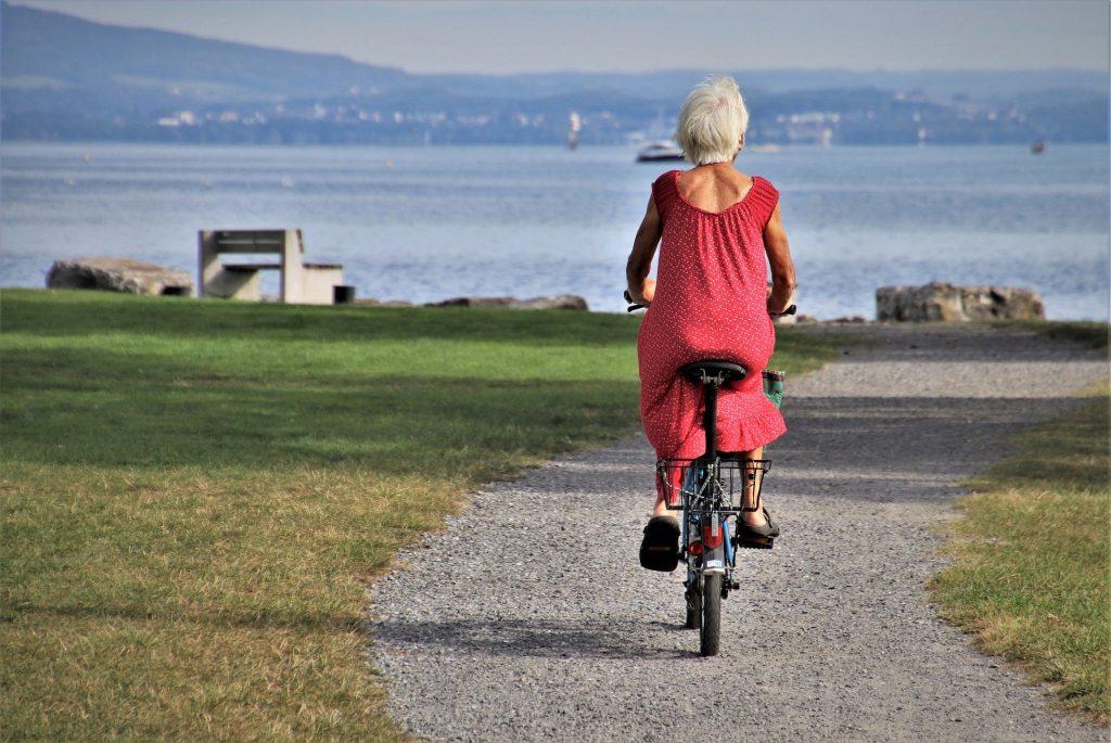 Imagem de uma senhora andando de bicicleta sozinha em uma estrada em direção ao mar. Ela usa um vestido vermelho.