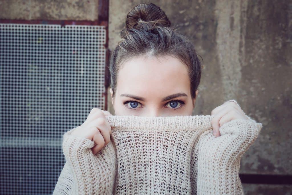 Mulher escondendo metade do rosto com a gola do blusão bege que está vestindo.