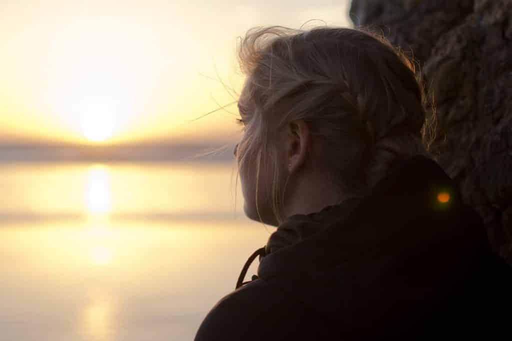 Mulher olhando para o pôr do sol em um rio.
