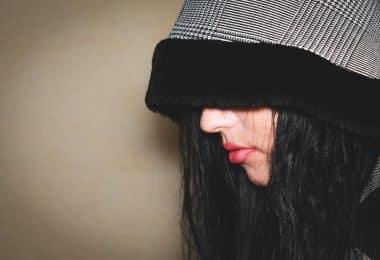 Imagem do rosto de uma mulher de lado. Ela usa uma touca cinza com barrado preto. A touca cobre toda a parte superior da cabeça e dos olhos. Ela está de mau humor.