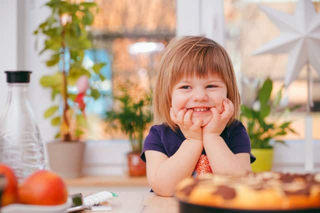 Menina sentada com braços apoiados na mesa e rosto apoiado nas mãos sorrindo