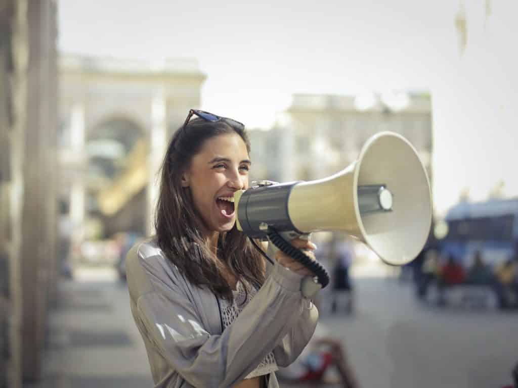 Mulher falando em um megafone.