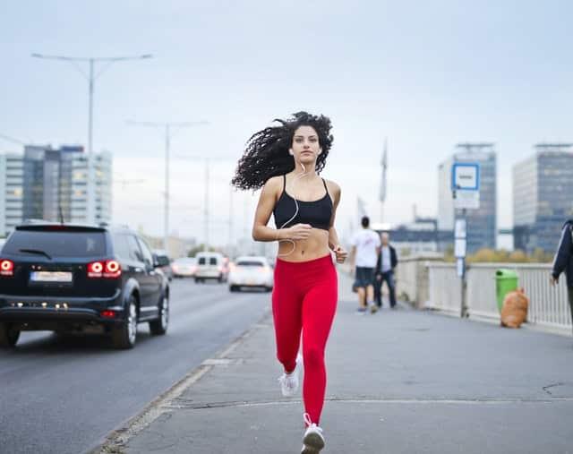 Mulher correndo com fones de ouvido e cidade ao fundo