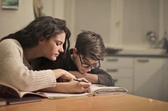 Irmã ajudando irmão com a lição de casa