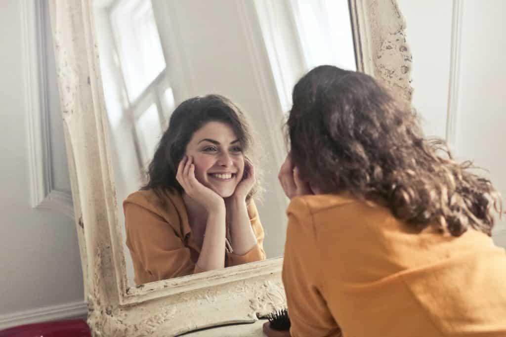 Mulher se olhando no espelho e sorrindo com o rosto apoiado nas mãos, demonstrando felicidade.