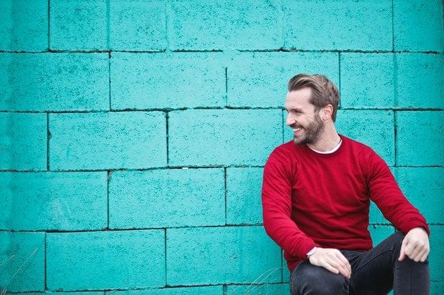 Homem sentado de perfil sorrindo em muro azul