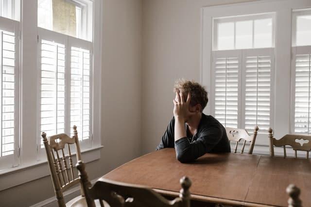 Homem sentado com braço apoiado em mesa e mão no rosto com janela entreaberta