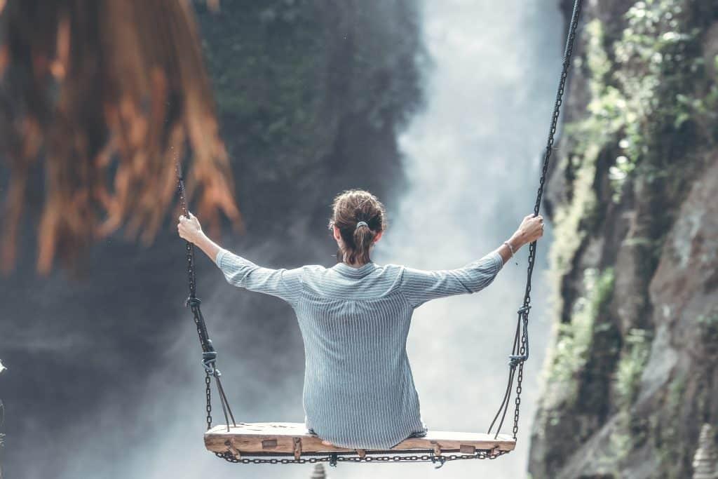 Mulher em um balaço de frente para uma cachoeira