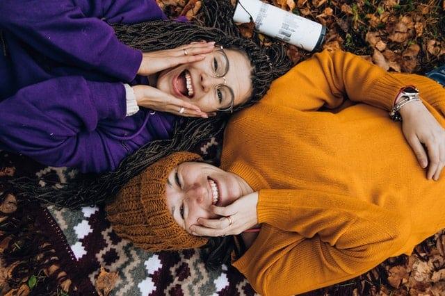 Amigas deitadas em pano vistas de cima sorrindo