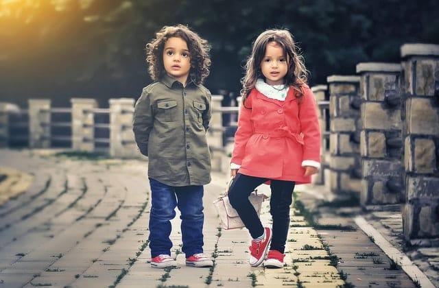 Casal de irmãos crianças em pé em ponte de pedra