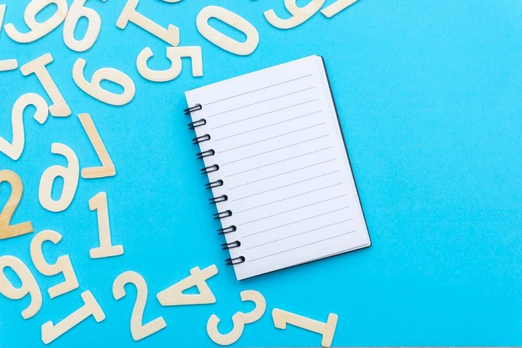 Caderno em branco em um fundo azul com números espalhados ao lado.