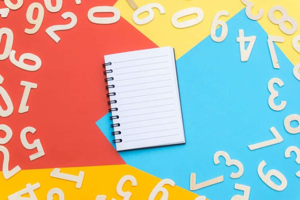 Caderno no centro de diversos números espalhados em um fundo colorido.
