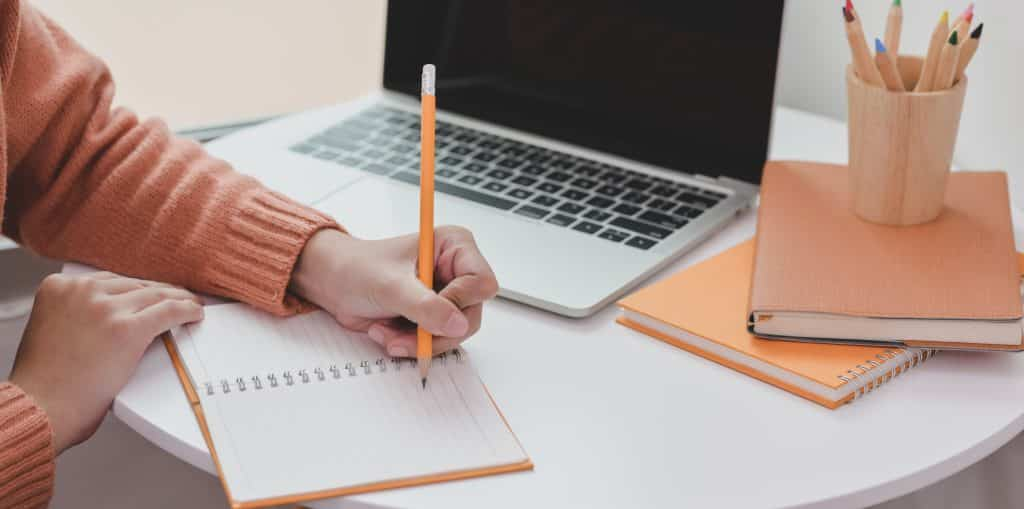 Mulher escrevendo em um caderno com um lápis