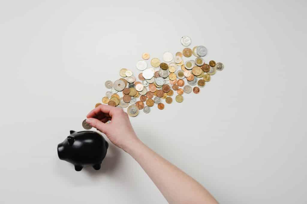 Cofre preto em formato de porco, como moedas ao lado e mão branca colocando moeda dentro do cofre.