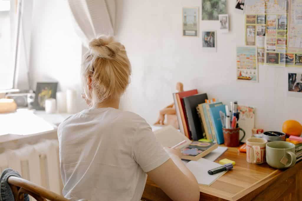 Mulher olhando para a janela segurando uma caneta em frente a uma mesa