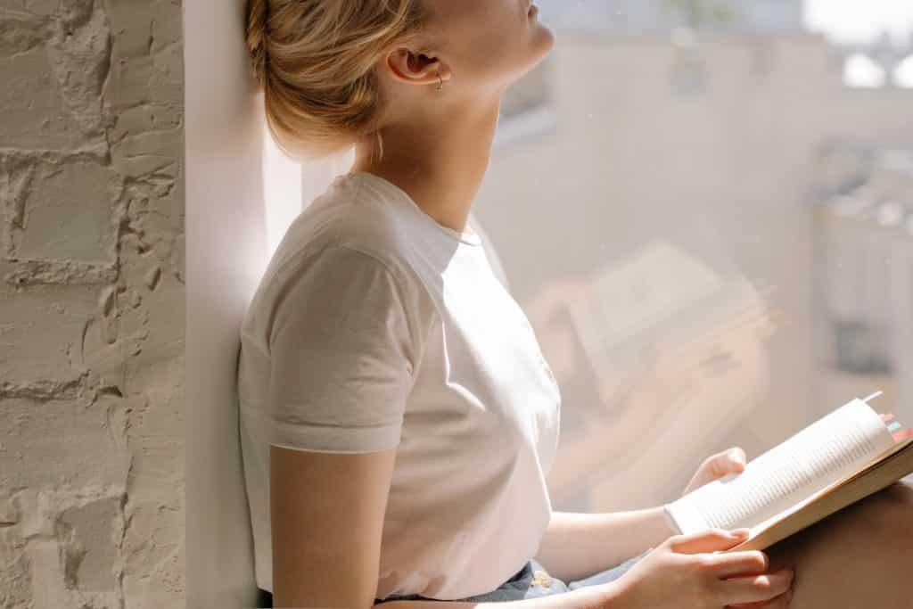 Mulher encostada em uma parede ao lado da janela segurando um livro