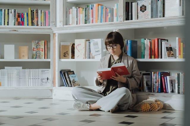 Mulher sentada no chão de biblioteca lendo