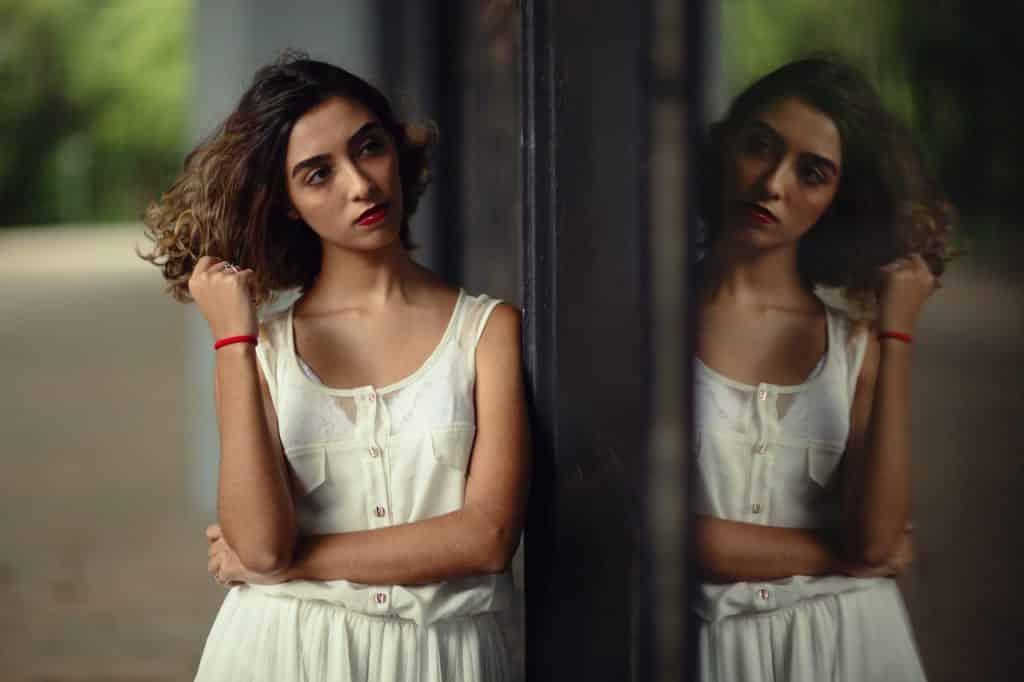 Mulher caminhando na rua enquanto mexe no cabelo e olha para o seu reflexo em uma vitrine.