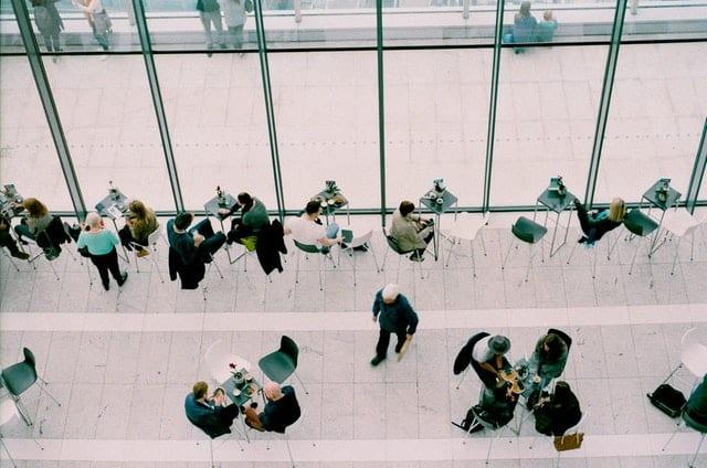 Mesas de praça de alimentação com pessoas vistas de cima