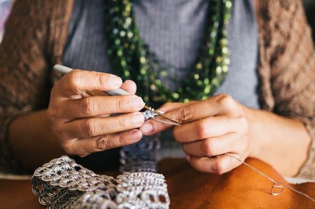 Mãos de mulher fazendo crochê visto de perto