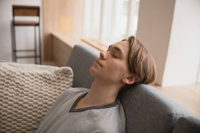 Homem em sofá com cabeça apoiada de olhos fechados