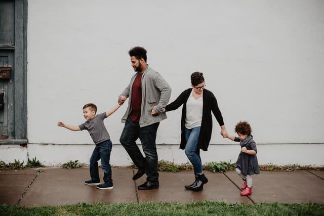 Pai e mãe de mãos dadas com filho e filha de mãos dadas andando juntos