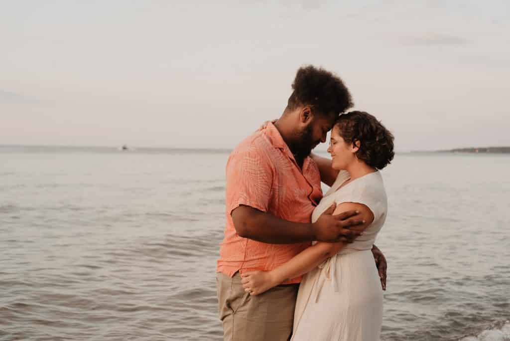 Homem e mulher abraçados e sorrindo ao lado do mar