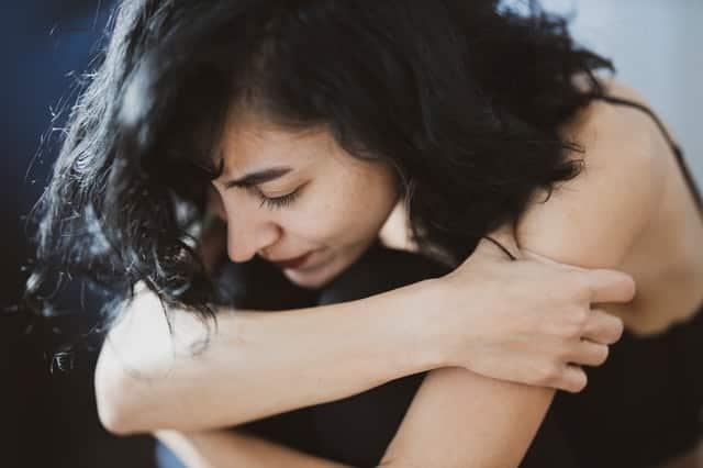 Mulher sentada com braços abraçando-se e expressão triste