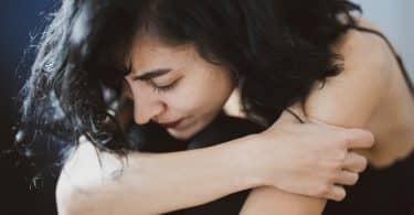 Mulher abraçando suas pernas com tristeza