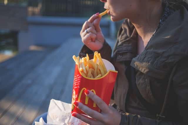Mulher de perfil comendo batata frita