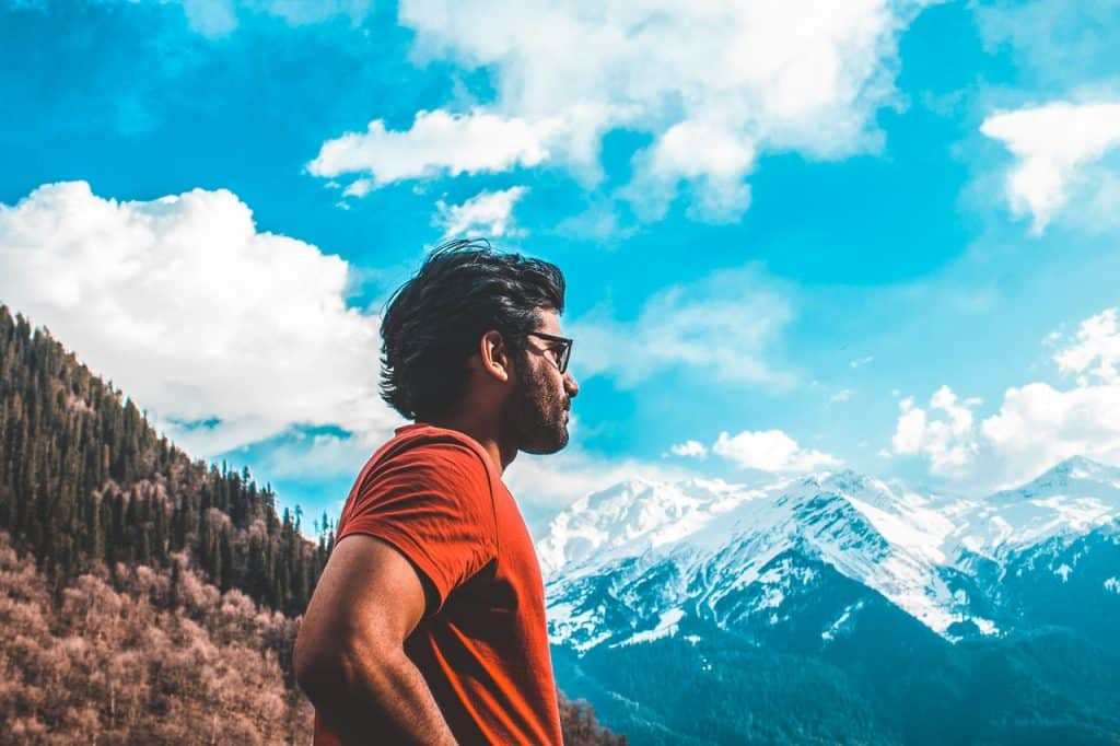 Homem de cabelos médios, usando um óculos preto e camiseta vermelha, observando as montanhas.