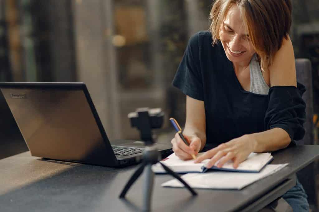 Mulher escrevendo em um caderno e sorrindo