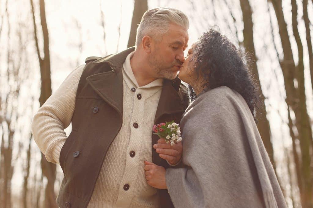 Homem e mulher se beijando ao lado de árvores