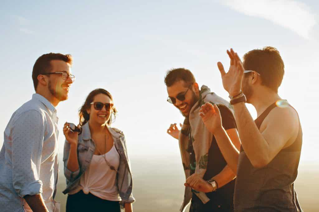 Três homens e uma mulher juntos sorrindo, demonstrando amizade e alegria.