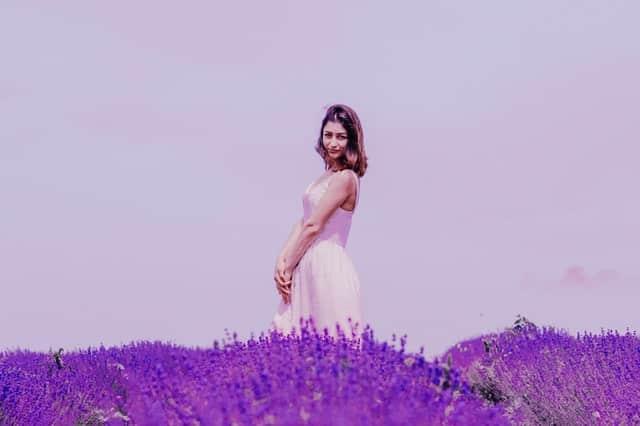 Mulher em pé em campo de flores roxa e céu ao fundo