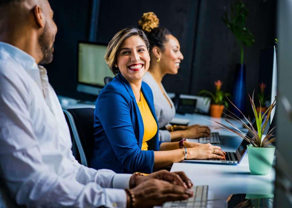 Três colegas de trabalho sentados em frente a computadores - a mulher que está no meio sorri para o homem ao seu lado.