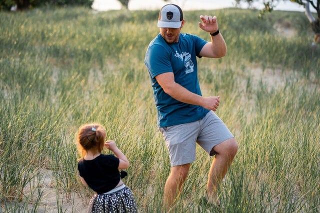 Pai e filha dançando em campo com mato baixo
